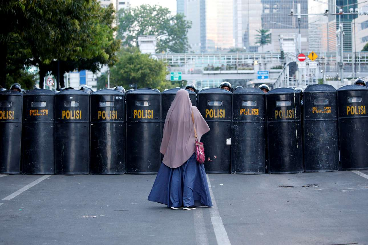 Στην Τζακάρτα της Ινδονησίας μία γυναίκα στέκεται μονάχη της μπροστά στο σιδηρόφρακτο τείχος των αστυνομικών περιφρουρούν το κτίριο της Ανώτατης Εκλογικής Επιτροπής. Οι πολίτες διαμαρτύρονται για τα αποτελέσματα που ανακοίνωσε η Επιτροπή