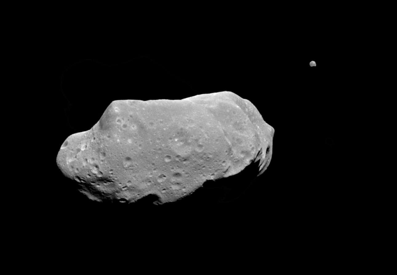 Ο αστεροειδής 243 Ida (δεξιά) και το μικροσκοπικό φεγγάρι (πάνω δεξιά), όπως φαίνονταν από το διαστημόπλοιο Galileo της ΝΑSΑ. Αυτή είναι μία από τις πρώτες φωτογραφίες που τεκμηριώνουν την ύπαρξη φυσικών δορυφόρων (αστεροειδών)