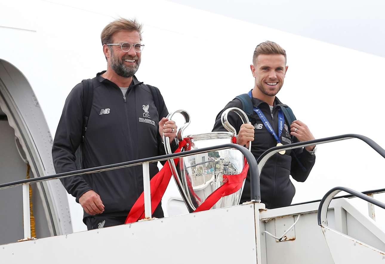 Η ώρα της άφιξης στο αεροδρόμιο «Τζον Λένον». O Γιούργκεν Κλοπ με τον Τζόρνταν Χέντερσον παρουσιάζουν το τρόπαιο του Champions League