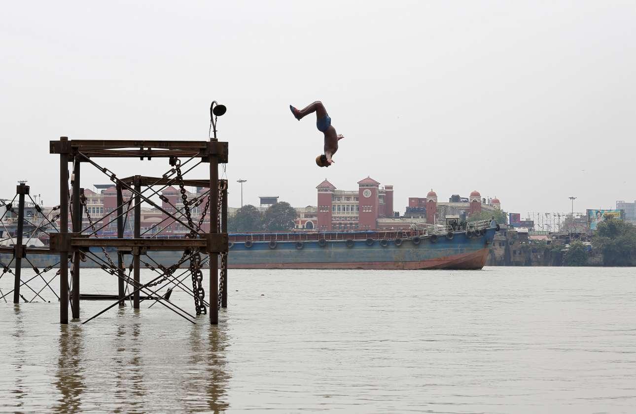 Aγόρι βουτά με θεαματικό τρόπο στα νερά του Γάγγη, στην Καλκούτα, για να δροσιστεί