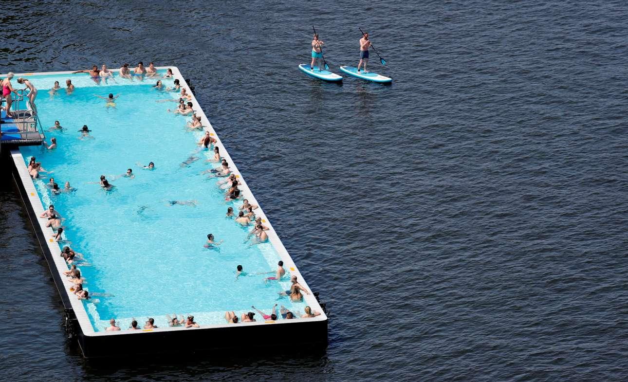 Κόσμος απολαμβάνει τον καλό καιρό στη φουτουριστικού σχεδιασμού πισίνα «Badeschiff» (πισίνα πλοίο) στον ποταμό Σπρέε, στο Βερολίνο