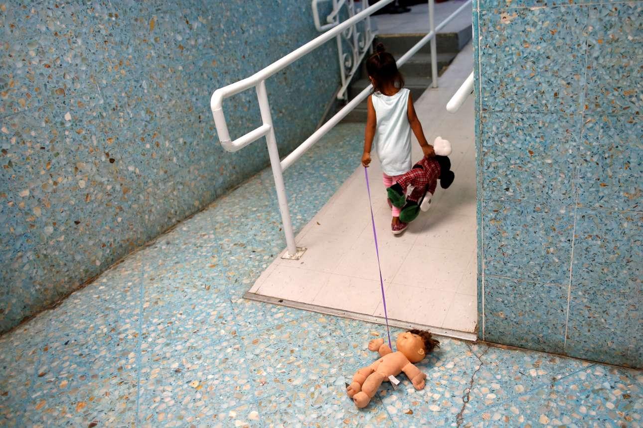 Κοριτσάκι από λατινοαμερικανική χώρα παίζει με τις κούκλες του σε διάδρομο στην εκκλησία «San Francisco Javier Church» στο Λαρέντο του Τέξας. Η Καθολική Εκκλησία χρησιμοποιείται προσωρινά ως καταφύγιο για τους μετανάστες που ζητάνε άσυλο στις ΗΠΑ