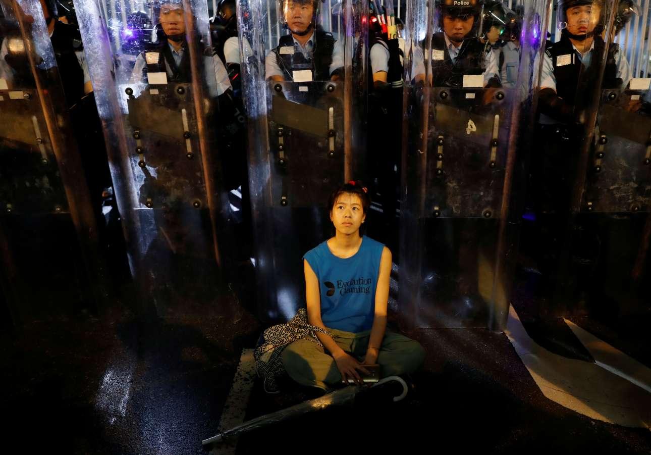 Διαδηλώτρια στέκεται μπροστά στις αστυνομικές δυνάμεις στο Χονκ Κονγκ. Χιλιάδες άνθρωποι διαμαρτύρονται ζητώντας την απόσυρση σχεδίου νόμου της κυβέρνησης που εγκρίνει τις εκδόσεις καταζητούμενων στην ενδοχώρα της Κίνας
