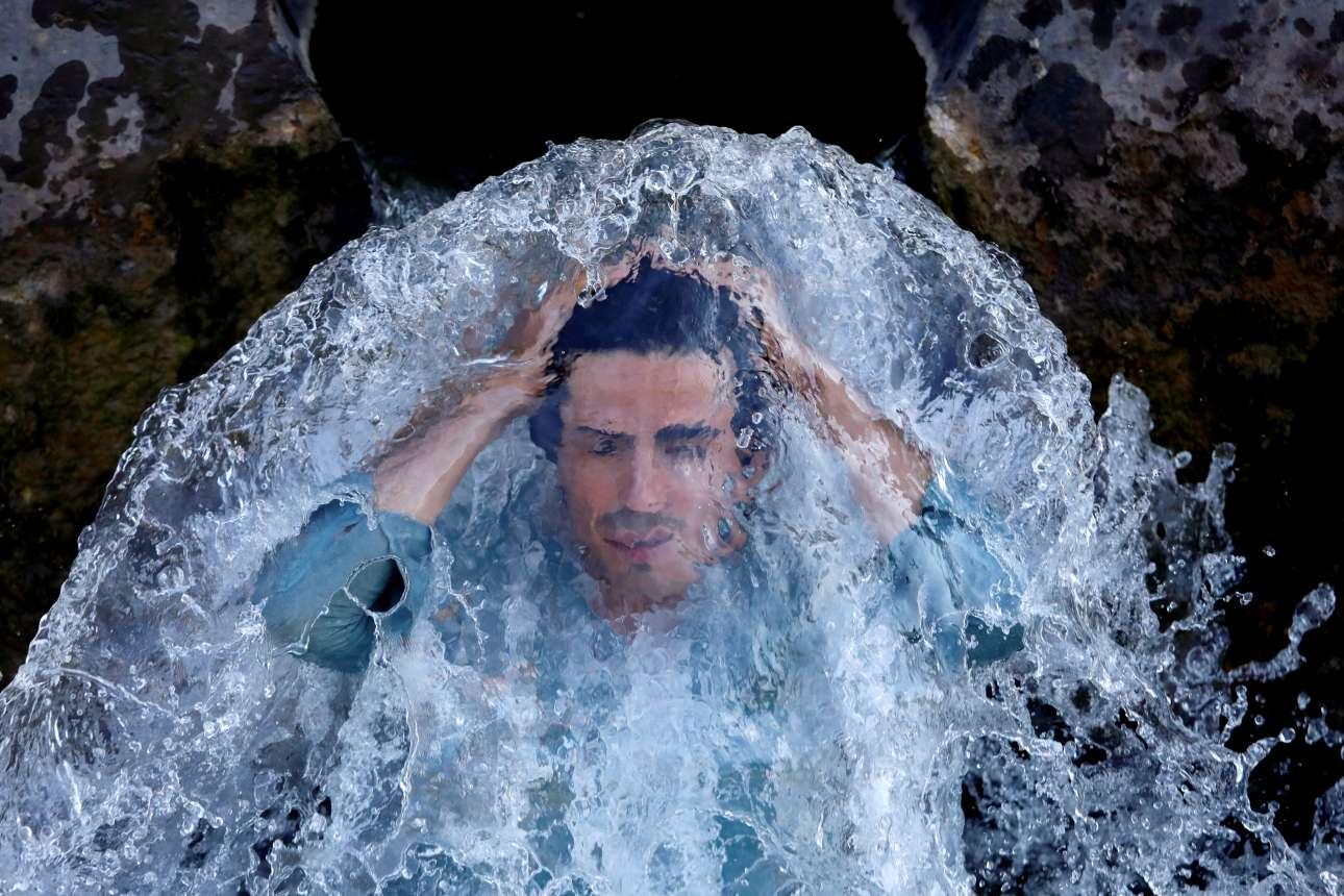 Ανδρας δροσίζεται με το τρεχούμενο νερό από σωλήνα στην πόλη Πεσαβάρ του Πακιστάν