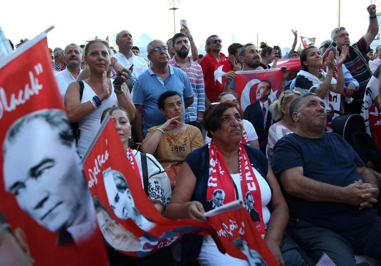 Λίγο πριν από τα πρώτα αποτελέσματα, οπαδοί του Ιμάμογλου κρατούν σημαίες με τον Κεμάλ Ατατούρκ