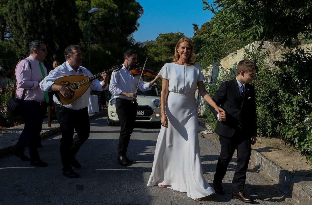Η νύφη καταφθάνει στην εκκλησία εν χορδαίς και οργάνοις. Τη συνοδεύει ο γιος της, καρπός του πρώτου της γάμου με τον εκδότη Πέτρο Κωστόπουλο