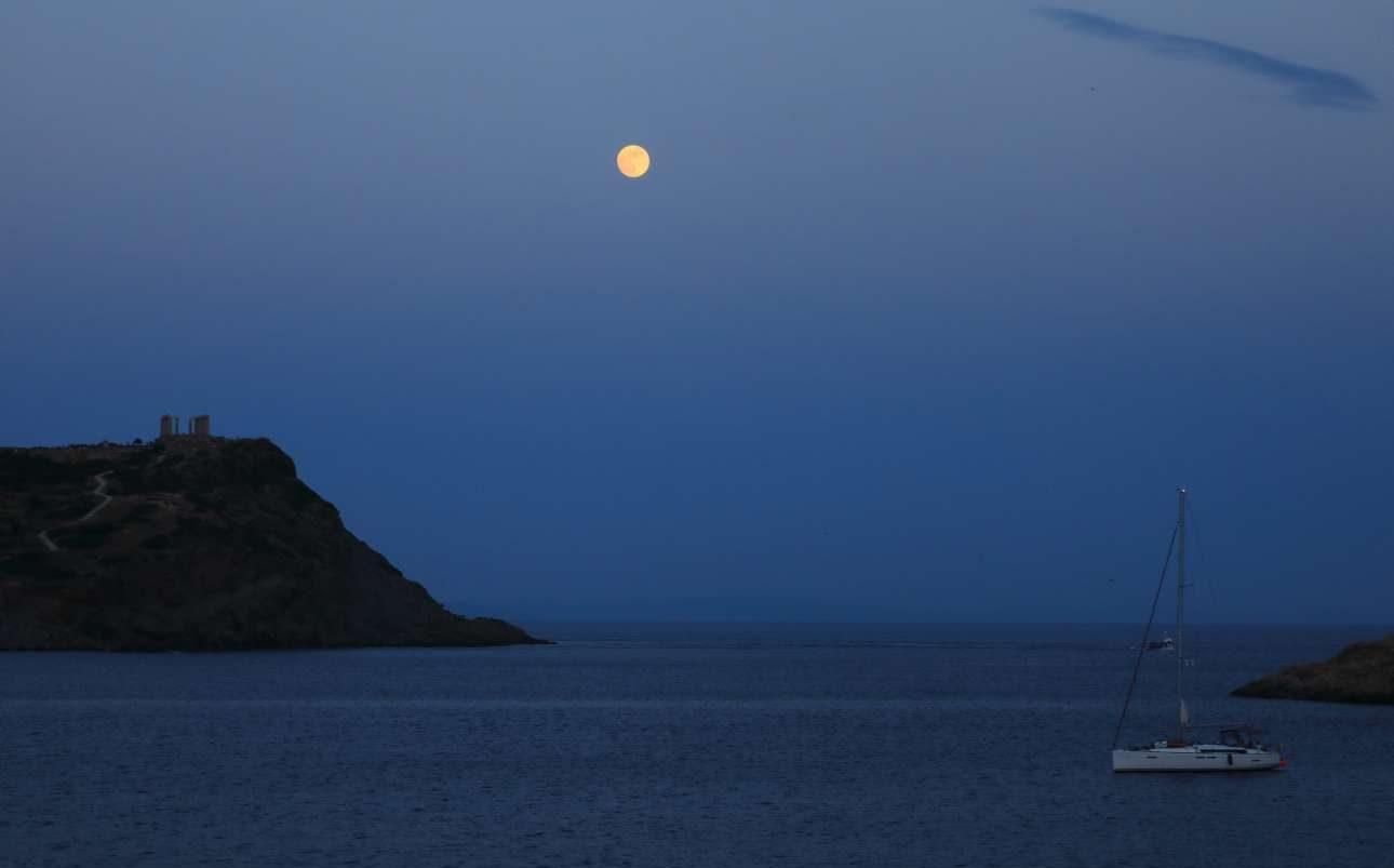 Υπέροχο ελληνικό καλοκαίρι. Η Πανσέληνος του Ιουνίου «λούζει» με τη λάμψη της τον Ναό του Ποσειδώνα και τον όρμο στο Σούνιο. Κάποιος έχει την τύχη να έχει και κότερο για βόλτα