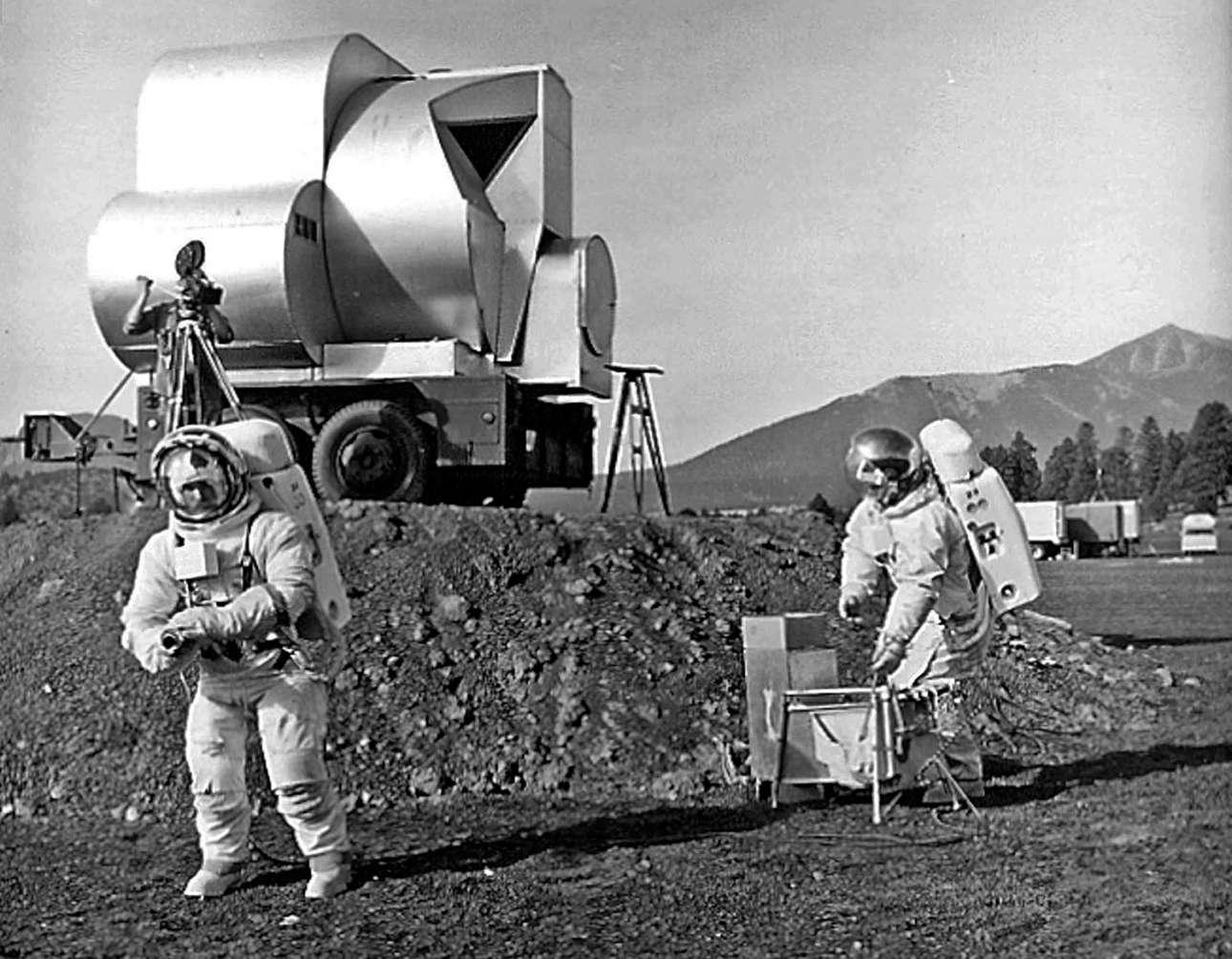 Οι αμερικανοί γεωλόγοι Τιμ Χάιτ και Ντέιβιντ Σλέιτσερ κάνουν εργασίες στην περιοχή Cinder Lake Crater Field φορώντας διαστημικές στολές και έχοντας πίσω τους ένα αντίγραφο σεληνακάτου