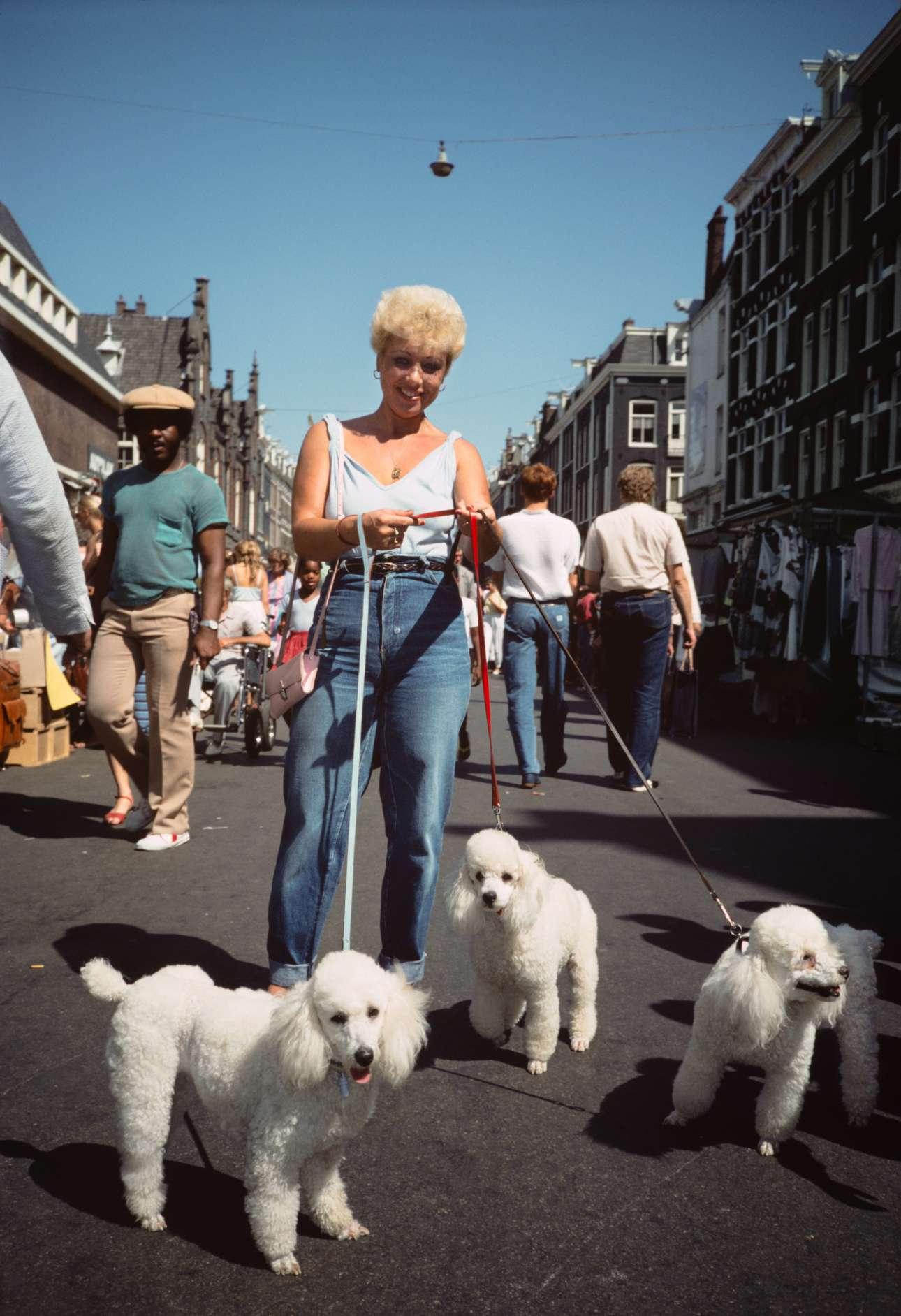 Γυναίκα βγάζει βόλτα τα σκυλιά της στην αγορά Albert Cuyp του Αμστερνταμ, το 1983