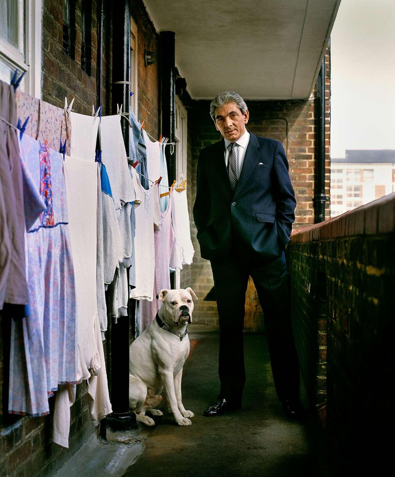 Ο βρετανοκύπριος γκάνγκστερ Τόνι Λαμπριανού, εκτελεστής για τους διαβόητους εγκληματίες δίδυμους Κρέι, ποζάρει με τον σκύλο του έξω από το διαμέρισμα της μητέρας του στο Λονδίνο, το 1983. Ζούσε εκεί έπειτα από την αποφυλάκιση του, έχοντας εκτίσει 15 έτη