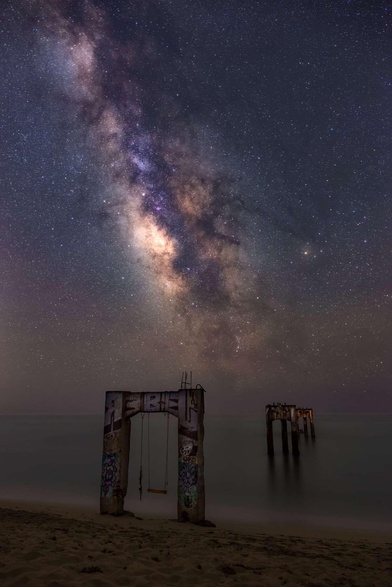 To κέντρο του γαλαξία μας λάμπει πάνω από την κατεστραμμένη πλατφόρμα του Ντάβενπορτ στις ΗΠΑ. Η πλατφόρμα χτίστηκε τον 19ο αιώνα για να μεταφέρεται ξυλεία προς την περιοχή του Σαν Φρανσίσκο αλλά αργότερα η διαδικασία αυτή σταμάτησε, η πλατφόρμα εγκαταλείφθηκε και έχουν απομείνει μόνο τα στηρίγματα της