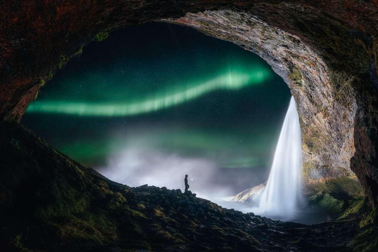 Ο καθαρός ουράνιος θόλος και το Βόρειο Σέλας φωτογραφημένα μέσα από μια σπηλιά στον καταρράκτη Seljalandsfoss στην Ισλανδία δημιουργούν μια μοναδικής ομορφιάς εικόνα που μοιάζει με πίνακα ζωγραφικής