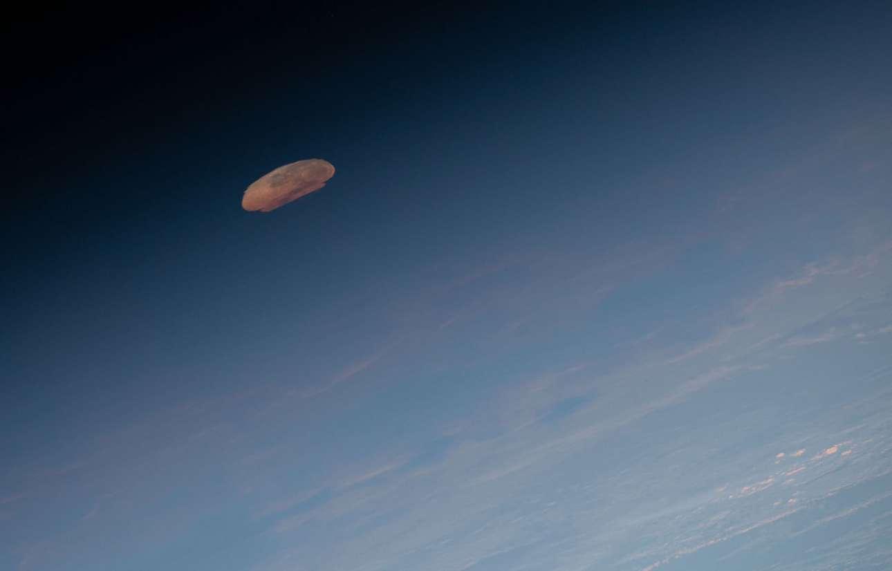 18 Μαΐου 2019. Το φεγγάρι φαίνεται παραμορφωμένο μέσα από πυκνά στρώματα της ατμόσφαιρας, καθώς ξημερώνει κάπου κοντά στη Βραζιλία