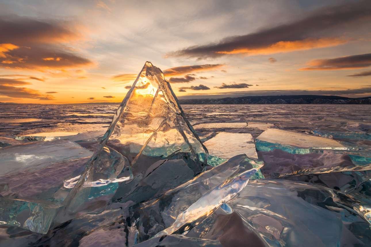Μαγευτικό ηλιοβασίλεμα πίσω από ένα τριγωνικό, διαυγές κομμάτι πάγου
