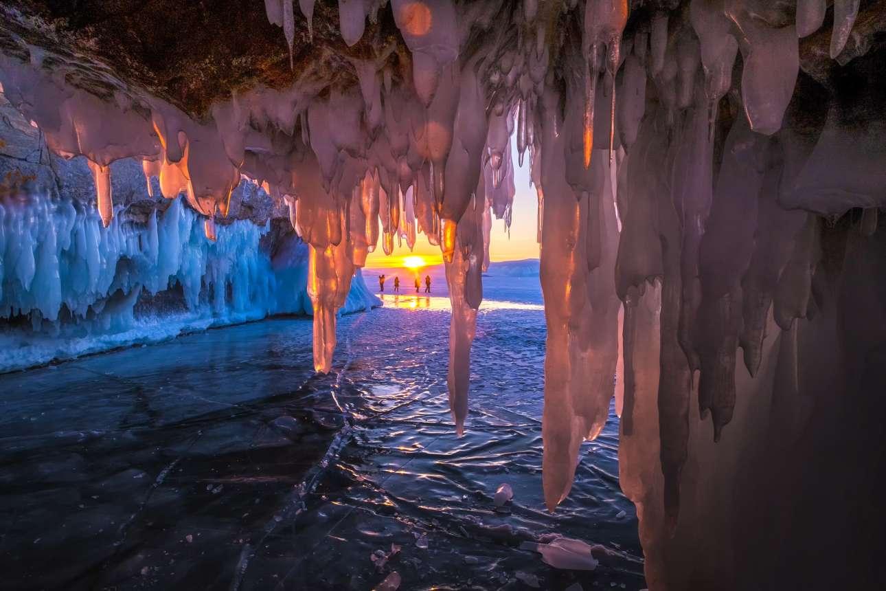 Σταλακτίτες από πάγο κρέμονται μέσα σε σπηλιά του νησιού Ολκχόν στη λίμνη. Στο φόντο ένα εκπληκτικό δειλινό
