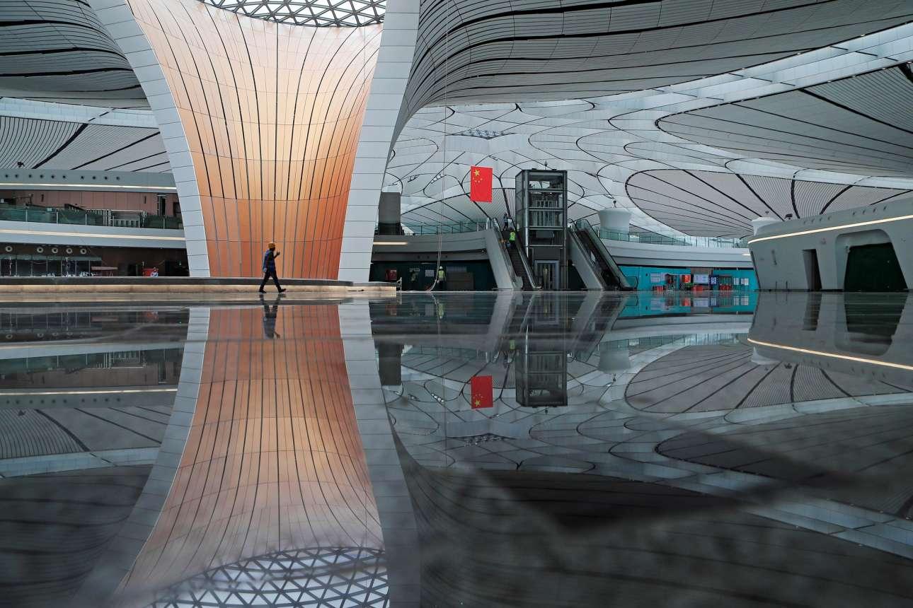 Ενας εργάτης διασχίζει το υπό κατασκευήν τέρμιναλ του νέου αεροδρομίου του Πεκίνου