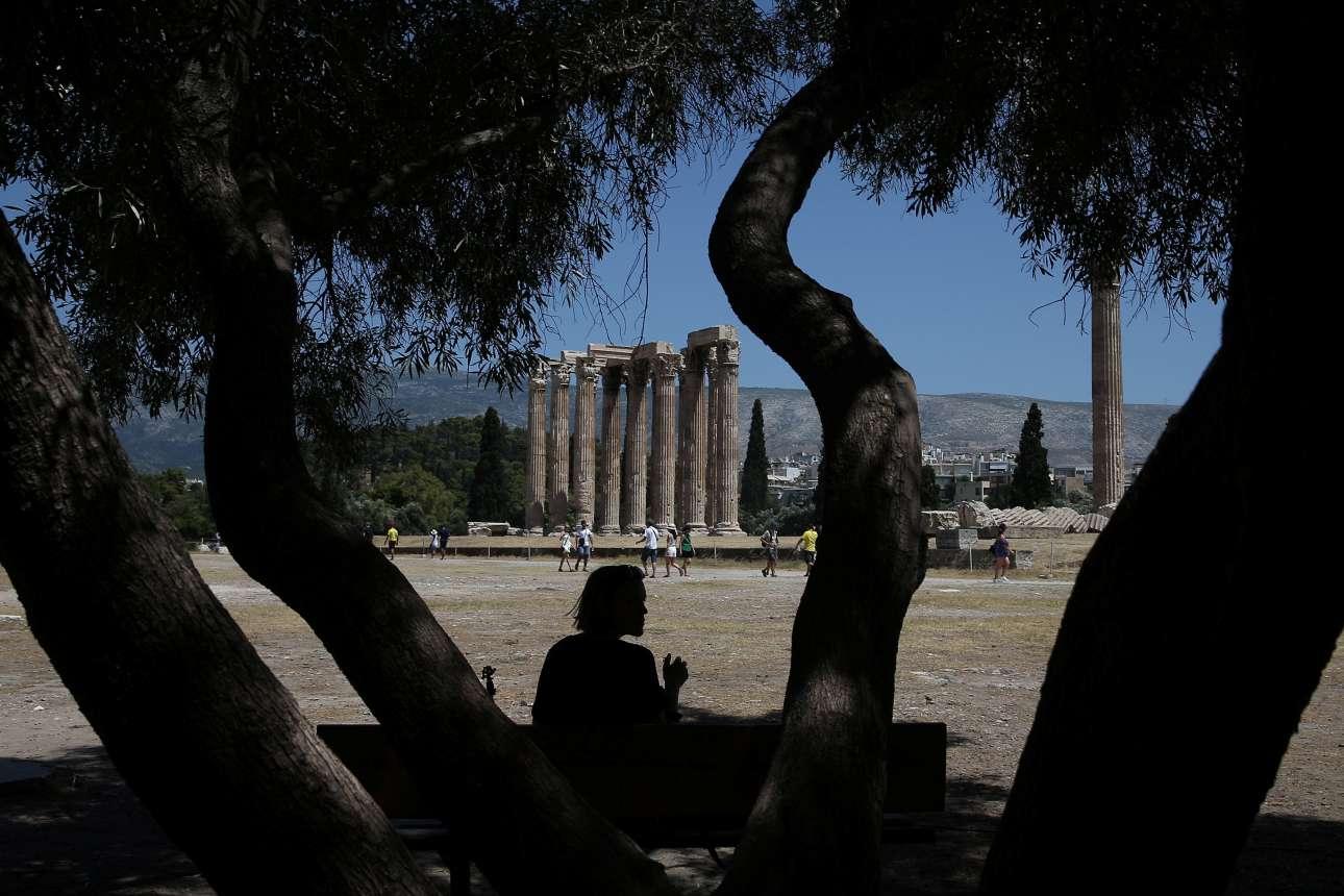 Τουρίστρια ξαποσταίνει στη σκιά ενός δένδρου στον αρχαιολογικό χώρο, στους Στύλους του Ολυμπίου Διός, στην Αθήνα