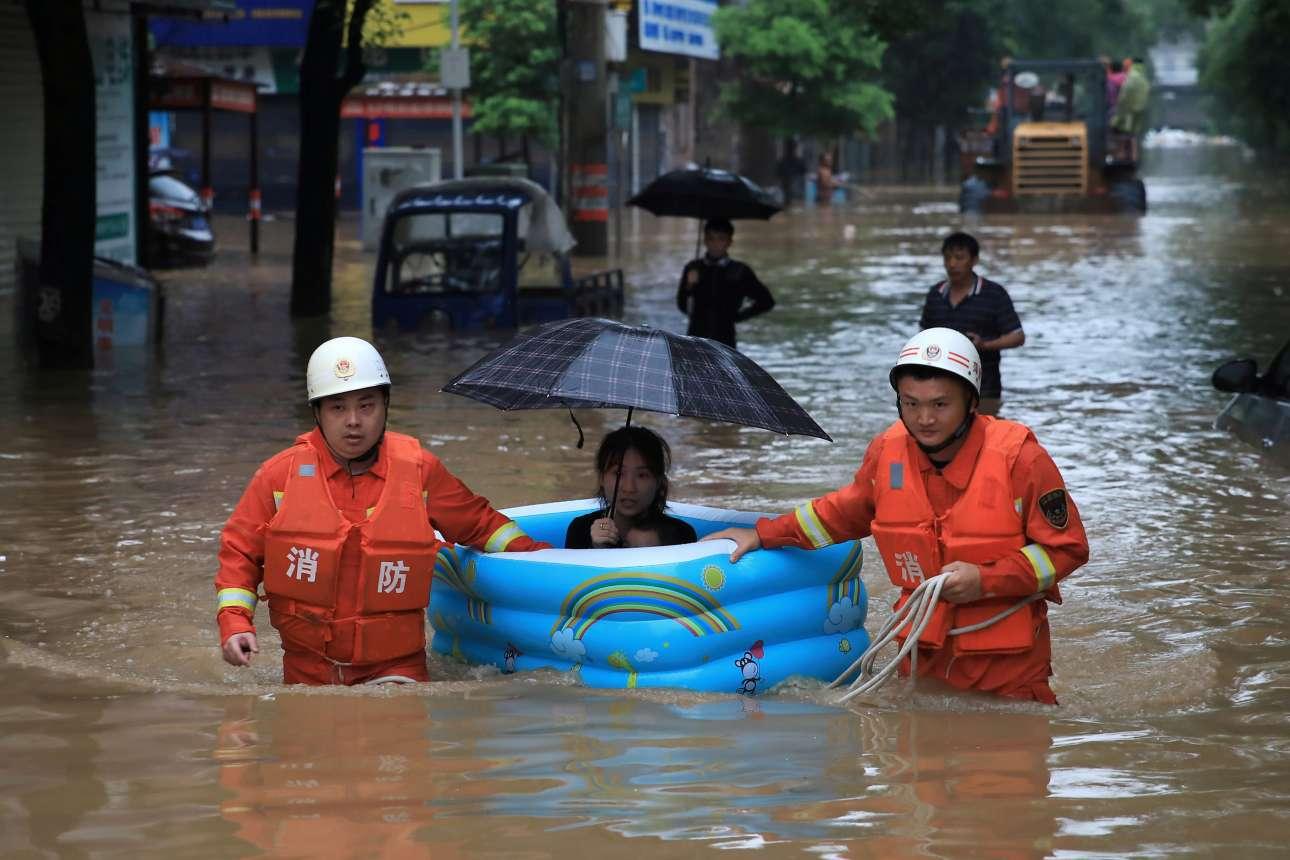 Διασώστες μεταφέρουν μία γυναίκα μέσα σε φουσκωτή πισίνα, καθώς δρόμοι πλημμύρισαν και σπίτια καταστράφηκαν μετά από πολύ ισχυρές βροχοπτώσεις σε περιοχή της επαρχίας Τσιανγκσί στην Κίνα