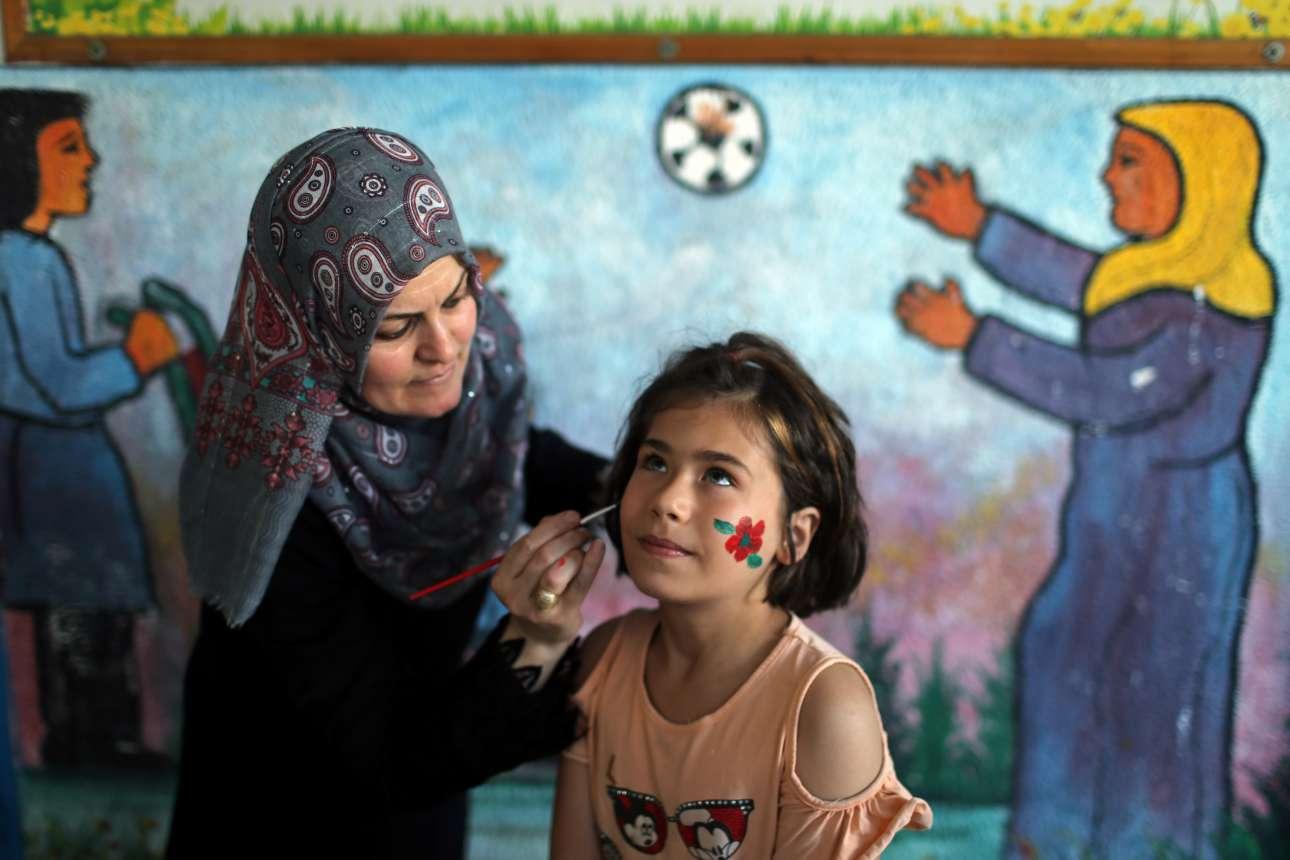 Mικρό κορίτσι από την Παλαιστίνη βάφει το πρόσωπό του σε θερινή κατασκήνωση που διοργάνωσε στην Γάζα το Γραφείο Αρωγής και Έργων του ΟΗΕ για τους Παλαιστίνιους Πρόσφυγες