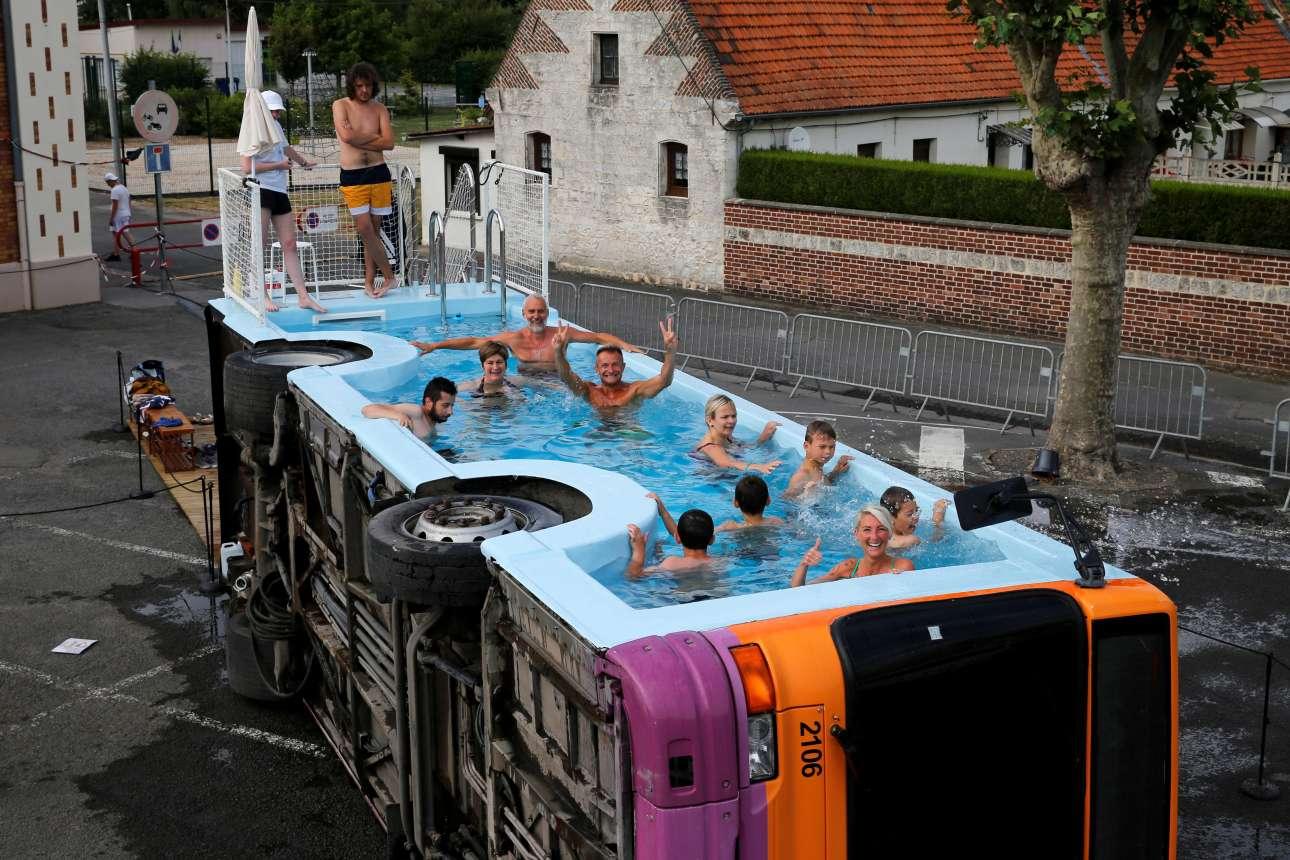 Κόσμος, στη γαλλική περιοχή Γκόσναϊ, κολυμπάει σε λεωφορείο που λειτουργεί ως πισίνα. Το λεωφορείο φέρει το όνομα «le bus piscine» και αποτελεί έργο του Γάλλου καλλιτέχνη Benedetto Bufalin