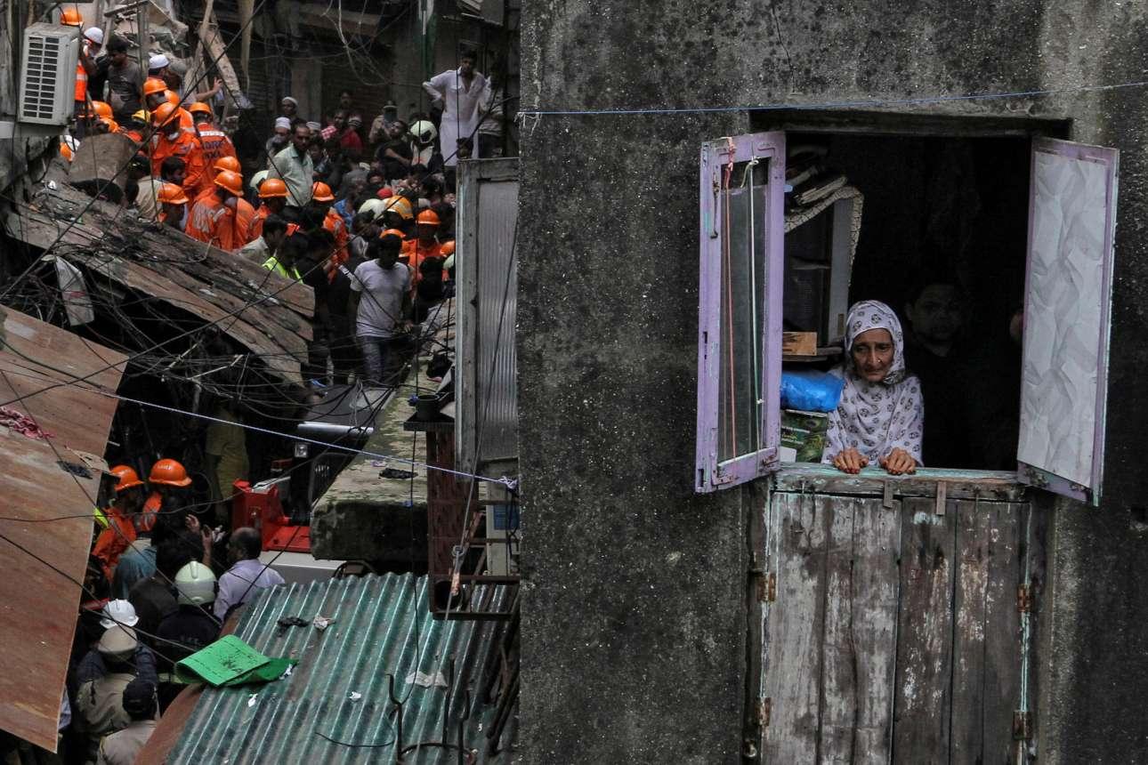 Μιλάει το βλέμμα μέσα από την παράγκα, στο Μουμπάι της Ινδίας, ενώ οι διασώστες ψάχνουν ψυχές στα ερείπια: «Γκρεμίστηκε το καλύβι του γείτονα. Μήπως ήρθε και η σειρά μου;»