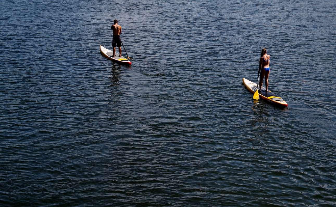Ένας άνδρας και μια γυναίκα κάνουν κανό στον ποταμό Δούναβη, στη Βιέννη