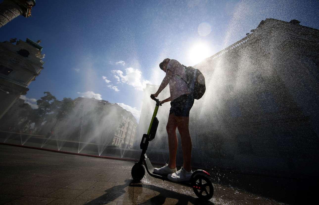 Άνδρας με σκούτερ περνά κάτω από συντριβάνια για να δροσιστεί στη Βιέννη