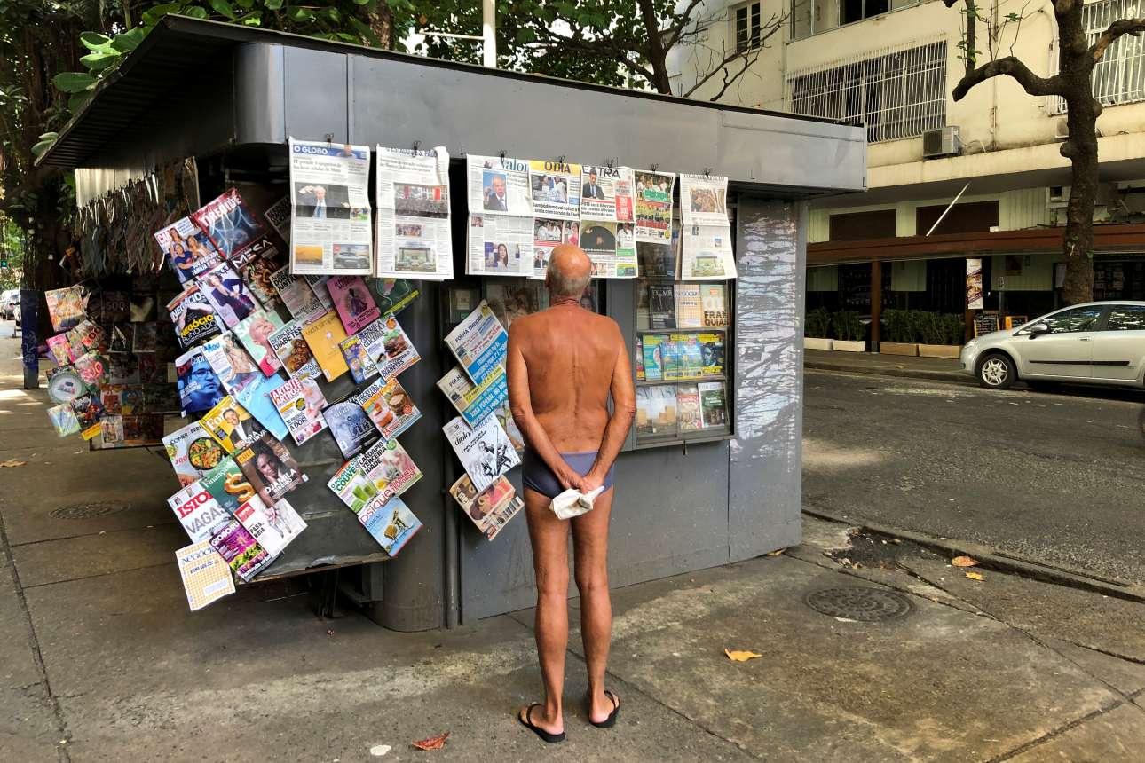 Η γυμνή αλήθεια; Ευτυχώς, όχι εντελώς. O ημίγυμνος κύριος χαζεύει τα πρωτοσέλιδα σε ένα κιόσκι κοντά στην παραλία Ιπανέμα του Ρίο