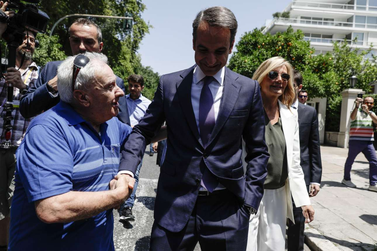 Ο Κυριάκος Μητσοτάκης δέχεται τα συγχαρητήρια ενός ανώνυμου περαστικού καθώς οδεύει προς το Προεδρικό για να ορκιστεί Πρωθυπουργό