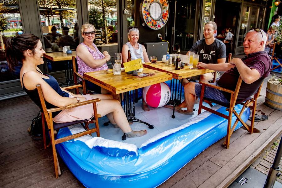 Ολλανδοί υποδέχονται τον καύσωνα στο εστιατόριο: τα πόδια τους μουλιάζουν στην πλαστική γούρνα και στο τραπέζι αφρίζουν οι μπιρίτσες. Ζήτω η ζέστη!