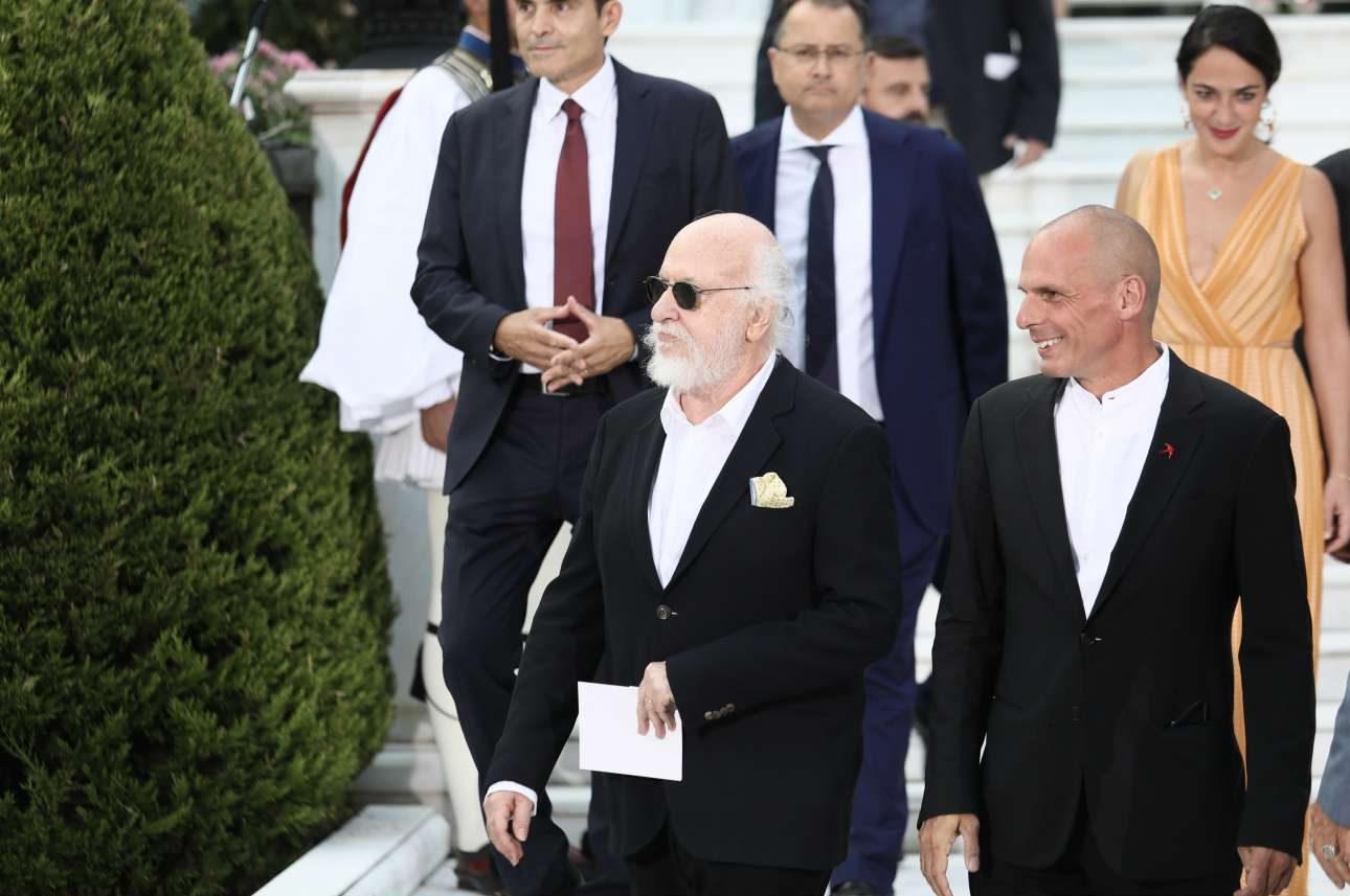 Ανέκφραστος ο Διονύσης Σαββόπουλος και χαμογελαστός ο επικεφαλής του ΜΕΡΑ25 Γιάν(ν)ης Βαρουφάκης, συλλαμβάνονται από τον φακό σαν (τυχαία) παρέα. Πίσω τους, χαμογελαστή, η υφυπουργός Εργασίας Δόμνα Μιχαηλίδου