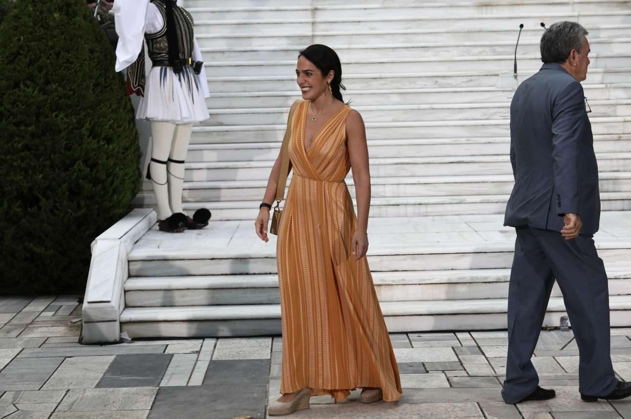 Η υφυπουργός Εργασίας Δόμνα Μιχαηλίδου δείχνει κεφάτη, αν και κάπως αμήχανη, ως πρωτάκι στα τελετουργικά της Ελληνικής Δημοκρατίας
