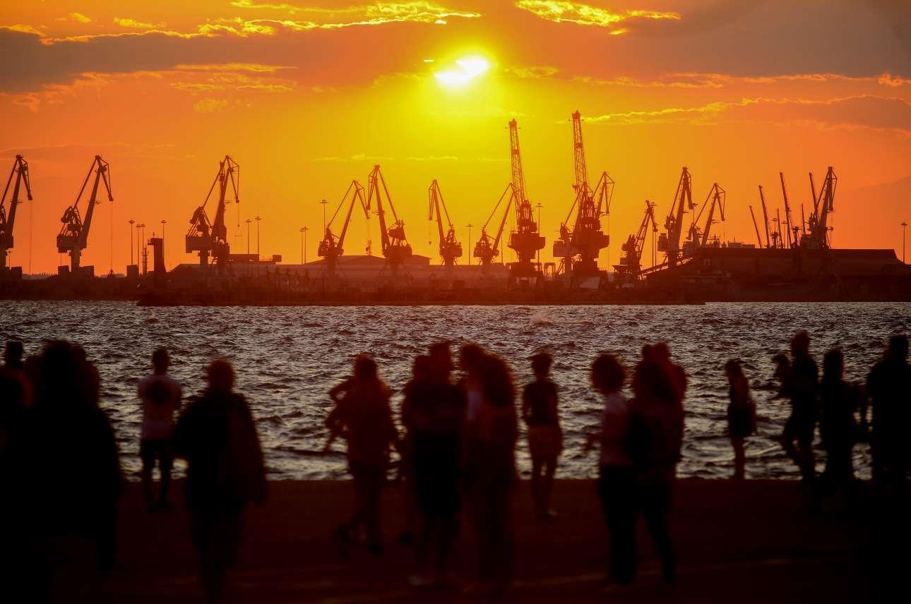 Χρυσοπόρφυρο ηλιοβασίλεμα πίσω από τους ντόκους με τα κρένια, στο λιμάνι της Θεσσαλονίκης, και ο κόσμος στην απέναντι μεριά, στην παραλία, χαζεύει το θέαμα