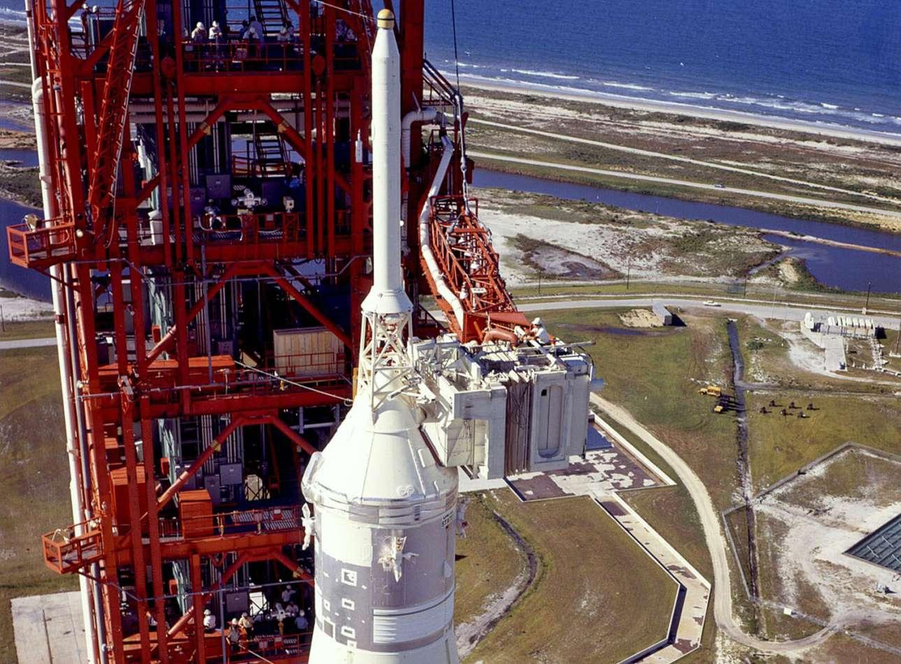 Ο πυραύλος ύψους 111 μέτρων Saturn V ετοιμάζεται για την εκτόξευση. Στην εικόνα διακρίνεται ένας τεχνικός να εργάζεται πάνω από την αίθουσα-φυσούνα από όπου θα εισέλθουν οι τρεις αστροναύτες
