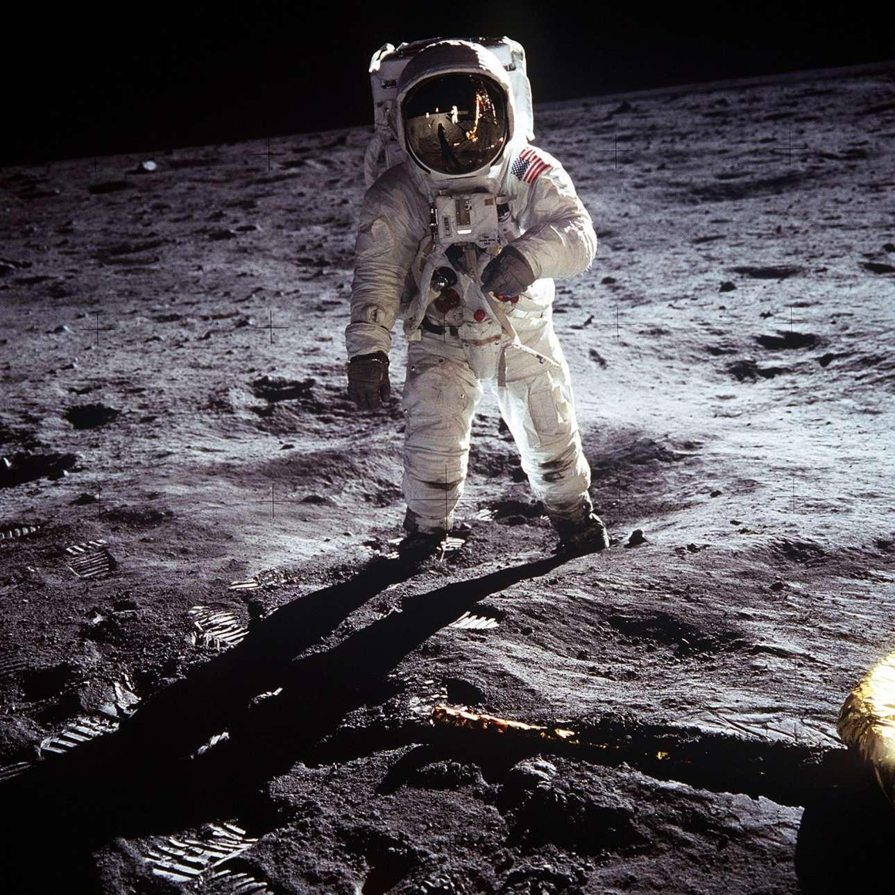 Οι δύο αστροναύτες -ο Νιλ Αρμστονγκ καθρεφτίζεται στην κάσκα του Ολντριν- θαυμάζουν το «υπέροχα έρημο τοπίο» του φεγγαριού