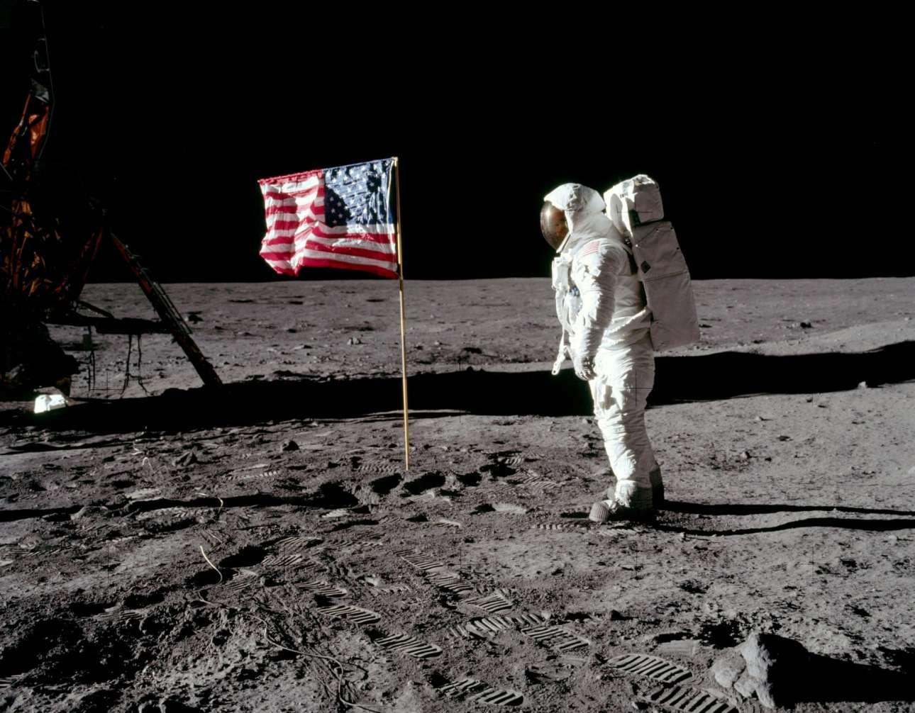 Ο Μπαζ Ολντριν ποζάρει δίπλα στην αμερικανική σημαία που ανεμίζει πάνω στην επιφάνεια της Σελήνης