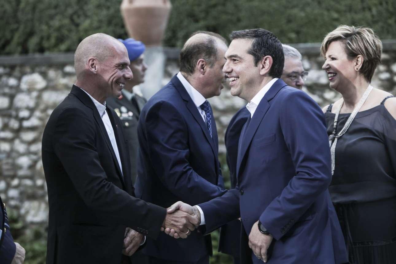 Πολλά χαμόγελα κατά τη χειραψία Τσίπρα - Βαρουφάκη, αλλά για... τρίτους: ο πρώην πρωθυπουργός κοιτάζει κάποιον μη διακρινόμενο, ενώ ο παλιός υπουργός του. μάλλον... κανέναν