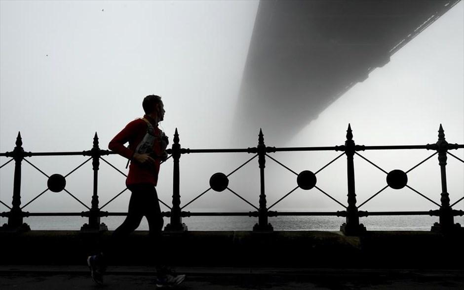 Ανδρας τρέχει κάτω από την Harbour Bridge στο Σίδνεϊ, καθώς η πόλη σκεπάζεται από ένα βαρύ πέπλο πρωινής ομίχλης