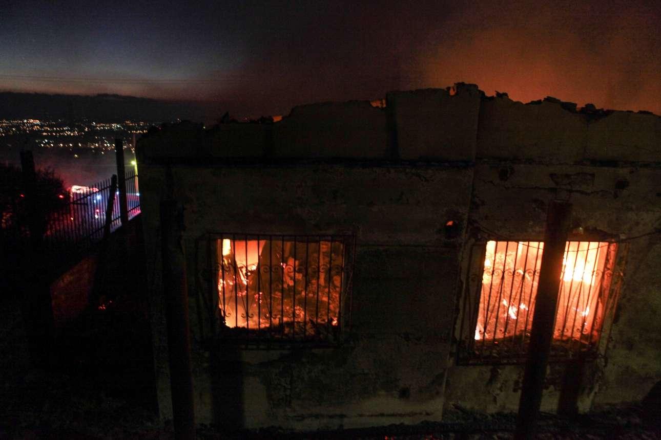 Ενα σπίτι έχει παραδοθεί στις φλόγες –με φόντο τα φώτα στα Μεσόγεια της Αττικής. Στο βάθος, η ανατολή πλησιάζει