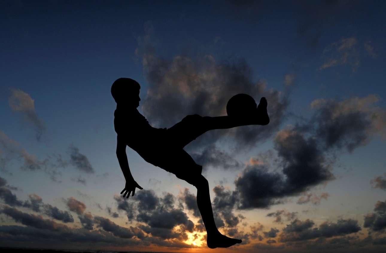 Νεαρός μπαλαδόρος κλωτσάει την μπάλα του σε παραλία στο Κολόμπο (Σρι Λάνκα)