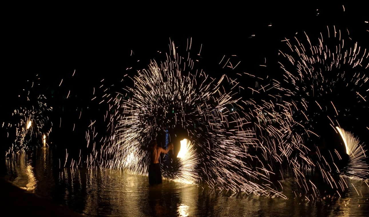 Σπίθες στη θάλασσα κατά τη διάρκεια τουριστικού σόου με φωτιές στην παραλία ξενοδοχείου στην Χουργκάντα (Αίγυπτος)