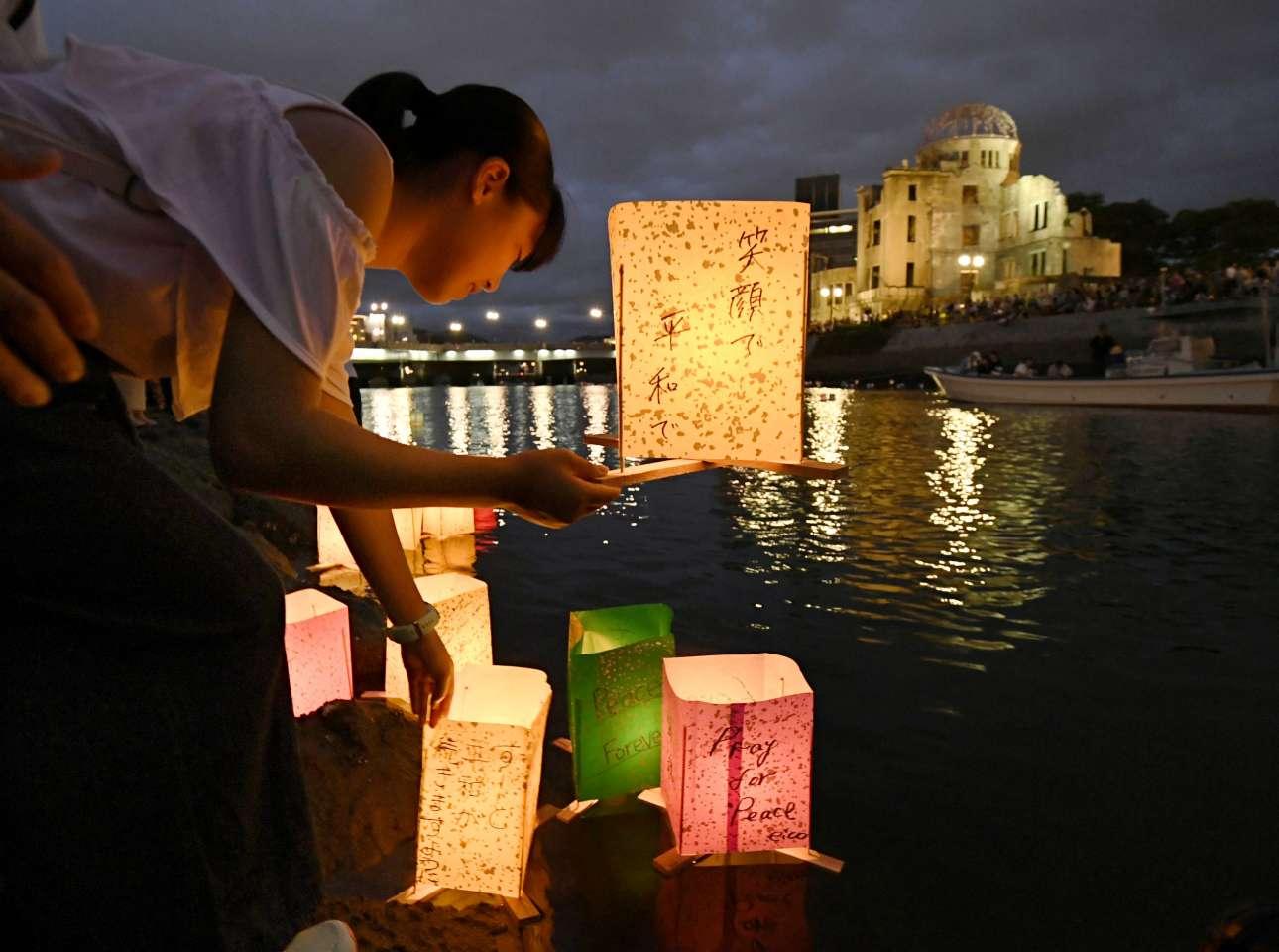 Μια κοπέλα αφήνει στο ποτάμι της Χιροσίμα χάρτινα φαναράκια στη μνήμη των θυμάτων της ατομικής βόμβας