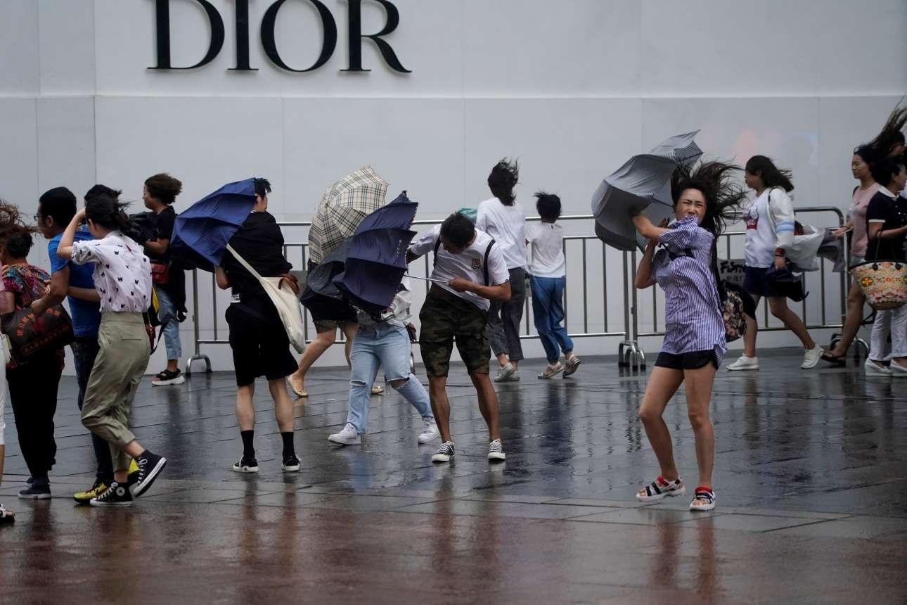 Στην Ελλάδα καύσωνας, στην Κίνα τυφώνες. Ανθρωποι προσπαθούν να αντιμετωπίσουν την δύναμη του αέρα κατά τη διάρκεια καταιγίδας στην Σανγκάη