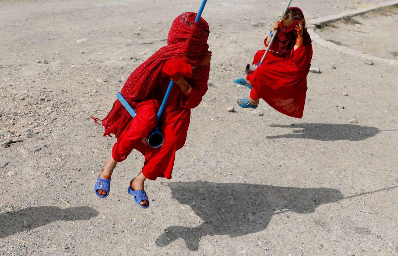 Ανεμελιά και καταπίεση στο ίδιο κάδρο. Δύο κορίτσια, ντυμένα από την κορφή ως τα νύχια, «απολαμβάνουν» ένα παιχνίδι κατά τη γιορτή του Ιντ αλ-αντχά στην -κατά τα άλλα «μετά τους Ταλιμπάν»- Καμπούλ του Αφγανιστάν...