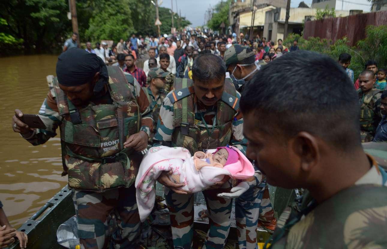 Στρατιώτης μεταφέρει ένα μωρό το οποίο διέσωσε σε επιχείρηση εκκένωσης της περιοχής Σανγκλί της ινδικής πολιτείας Μαχαράστρα. Οι πλημμύρες που προκάλεσαν οι σφοδρές βροχοπτώσεις του μουσώνα στη νότια και δυτική Ινδία έχουν προκαλέσει τον θάνατο τουλάχιστον 144 ανθρώπων και τον εκτοπισμό εκατοντάδων χιλιάδων άλλων, γνωστοποίησαν οι ινδικές Αρχές