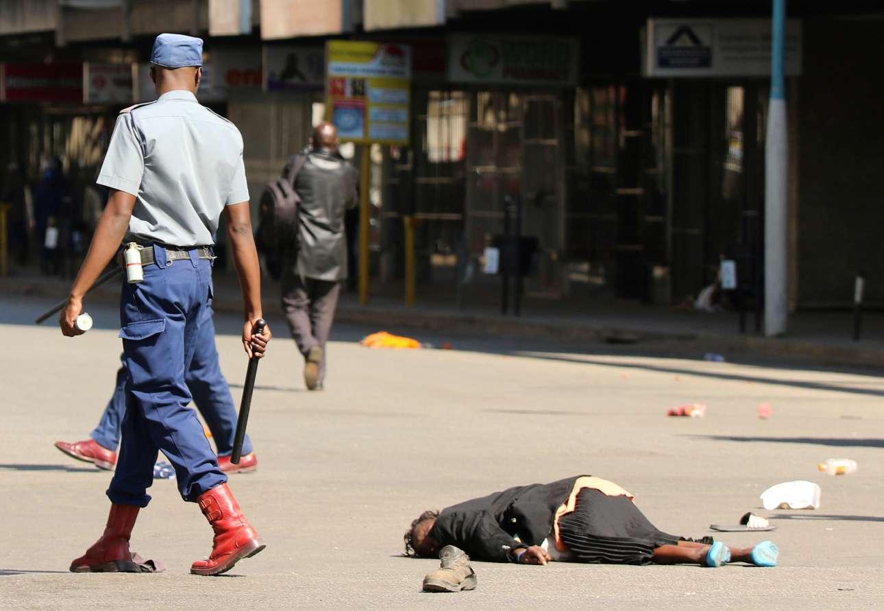 Αστυνομικός με το γκλομπ στο χέρι προσπερνά μια τραυματισμένη γυναίκα κατά τη διάρκεια της επεισοδιακής αντικυβερνητικής διαδήλωσης της 16ης Αυγούστου στη Χαράρε της Ζιμπάμπουε. Οι διαδηλωτές διαμαρτύρονταν για τη λιτότητα και το κόστος ζωής