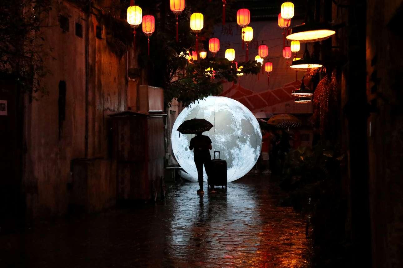 Ταξιδιώτης κάθεται μπροστά σε ένα μικρό φεγγάρι που έχει στηθεί στην Κουάλα Λουμπούρ μία βροχερή ημέρα στην Μαλαισία