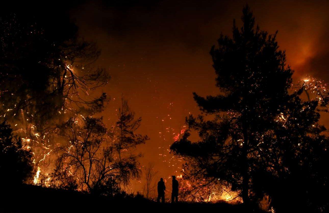 Δύο ανθρώπινες φιγούρες διακρίνονται μπροστά στο φλεγόμενο δάσος