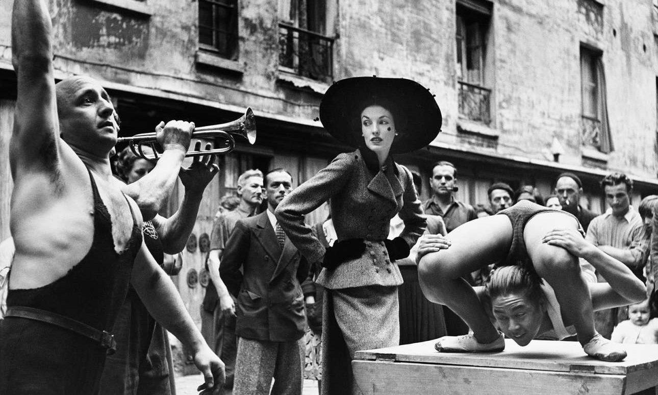 Παρίσι, 1948: το μοντέλο Ελίζ Ντάνιελς ντυμένη με κοστούμι Balenciaga ποζάρει ανάμεσα σε περφόρμερ του δρόμου
