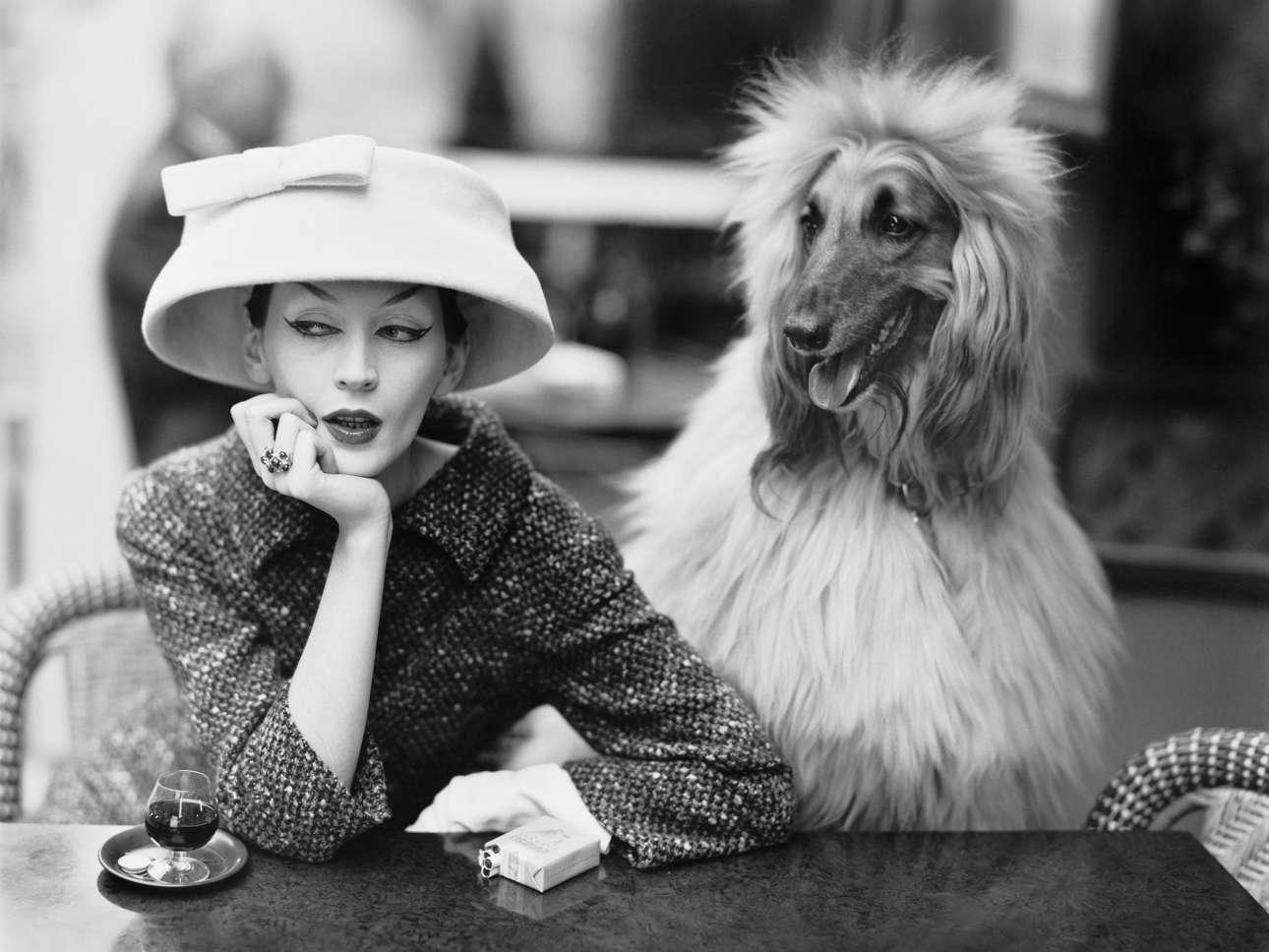 Το μοντέλο Ντοβίμα φορώντας Balenciaga κοστούμι και καπέλο ποζάρει στο θρυλικό παριζιάνικο καφέ «Les Deux Magots», το 1955